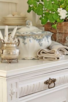 Silver sugar pot, white and blue soup tureen, white geranium in clay pot, and natural weave linens. From: VIBEKE DESIGN