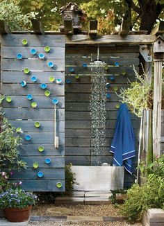 outdoor shower with Wall Play sculptures on fence.  Flora Grubb
