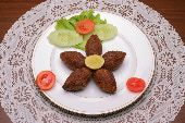 East Kibbeh recipe: Ground lamb, spices all rolle dup into a football shaped dumpling that is savory and delicious