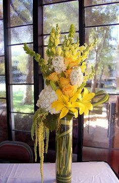 yellow lilies, white hydrangeas, yellow roses, white stocks, yellow snapdragons, green bells of irelands, green hanging amaranthus and pandanus leaves