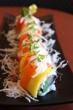 Blue Fin Sushi Bar in CA: Blue Fin Roll with tuna, yellow tail and asparagus topped with salmon and mango.