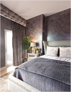 Austin bedroom walkout gray bedding gray drapes gray headboard gray walls layers of texture light wood floor mirrored nightstand potted plant textured bedding textured walls