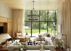 The family room's lounge chair is by Sutherland, the sectional sofa is by Flexform, and the glass table lamp at left is by Saladino Furniture; the curtains are of a Donghia fabric.