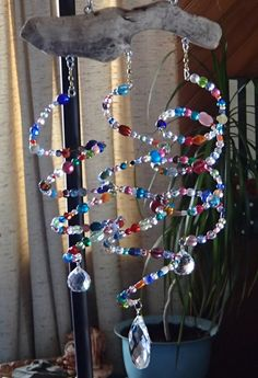 Glass beads strung on memory wire, with crystals, hung with fishing spinners, from driftwood.