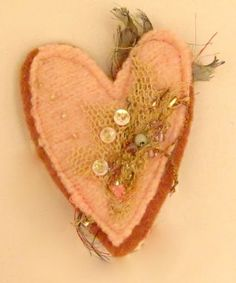 Small bits of lace, felted wool sweater, beads and fibers makes a sweet brooch by Jenny.