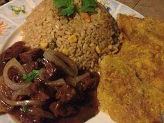 Arroz con consome y vegetales y carne de res en salsa de cebolla y tostones.