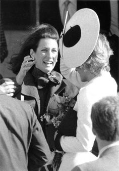 Princess Diana almost loses hat in the wind.