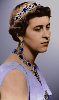 A hand-coloured image of the same parure, worn by Princess Sophie of Hesse, nee Greece (Duke of Edinburgh's  older sister) married Prince Christoph of Hesse in 1930. The tiara designed as five large amethysts, though some say sapphires, interspersed with foliate diamond spacers including smaller amethysts, and held between diamond bands top and bottom.