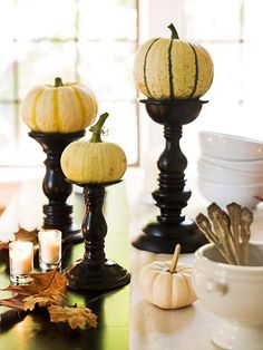 White pumpkins look striking when perched on dark wood candlesticks. Arrange your display on a dining room table or fireplace mantel.