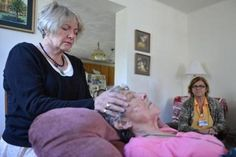 Hospice chaplain Nan Moore, a Unitarian Universalist chaplain performs a Reiki treatment during a home visit to Theresa Henderson of Natick.