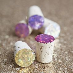 Glitter + Mod Podge Dimensional Magic is all you need to add a sparkly, 'glass-like' finish to the tops corks! For only $0.60 each!
