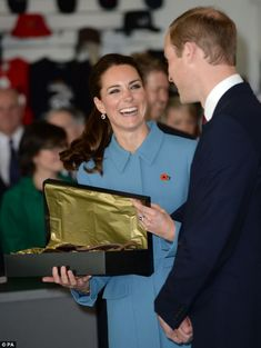 Kate and William laugh together after receiving a baby-sized flying hat at a WW1 Aviation Commemorative event in Blenheim during their official tour in New Zealand