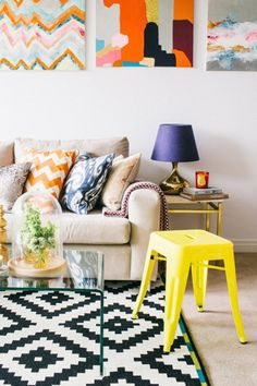 Colorful + graphic living room balanced by white walls and neutral couch