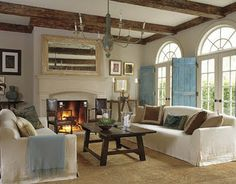 Barbara Westbrook. Gorgeous rustic living room, beamed ceilings, carved stone fireplace mantel, linen slip dove red sofas, french blue interior shutters