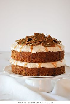 Pumpkin cake with cinnamon cream cheese frosting, salted caramel drizzles and a pumpkin-seed brittle topping. Perfect for fall celebrations. By Carrie Sellman for TheCakeBlog.com.