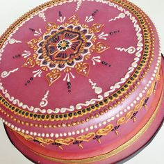 An angled view of this rose pink, gold, black and pearl white henna cake. The mandala design is iced on in royal icing and then painted over with edible metallic paint.