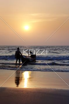 Ready to Fish - Two men pushing their boat into the sea on Pollethai Beach, India.