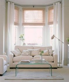 Cream colored living room with big soft couch against bay window with sheer drapes