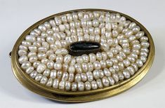 Rare Mongolian barrette. A brass medallion is filled with pearls, surrounding a black agate.