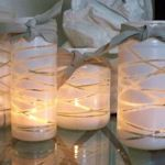 Old jars are wrapped with yarn in crisscross pattern then spray painted. Genius and cute!