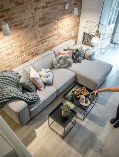 Beeld via de website vanLovingit  Wat een prachtigen warm beeld van een woonkamer. Stiekem blijft de bakstenen muur gewoon erg mooi en leuk in combinatie met een strakke grijze hoekbank. Een knoopkussen is een grappig detail, net als het grote grof gebreide plaid (die hoog op mijn lijstje staat om nog eens zelf te