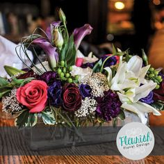 Centerpiece by Fleurish Floral Design | Hot Pink Roses, Black Bacara Roses, White Roses, Purple Carnations, Rice Flower, Asiatic Lilies, Green Hypericum Berries, Purple Lisianthus, Burgundy Mini Calla Lilies, Purple Trachelium, Red Spray Roses, with Bear Grass and Variegated Pitt