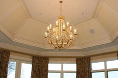 Large, sophisticated home design with #chandelier and tall windows.