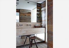 A arquiteta Cristina Bozian desenvolveu uma prateleira para os produtos de higiene pessoal: o espelho corre pela parede e deixa à mostra ora as prateleiras, ora a janela. A bancada de mármore travertino tem espaço para duas torneiras