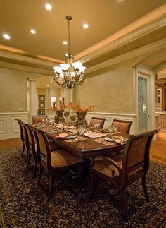 Large dining room with column-framed doorways, wood paneling on the walls, wood floor, large floor rug and massive wood table with seating for ten people.