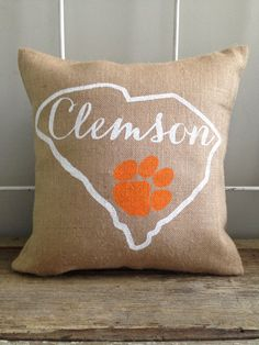 Burlap pillow with Clemson and the tiger paw hand painted inside an outline of the state of South Carolina Hand painted white and orange on