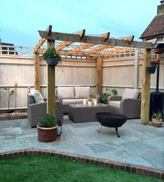Rattan garden furniture placed under the pergola with fairy lights, plants and a fire pit to create the perfect cosy outdoor space! Patio Diy, Patio Pergola, Backyard Patio Designs, Backyard Landscaping, Landscaping Design, Small Backyard Patio, Small Pergola, Modern Pergola, Pergola Ideas