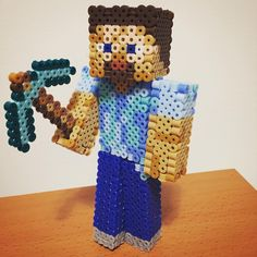Steve with a diamond pickaxe from the game Minecraft. Made with perler beads.