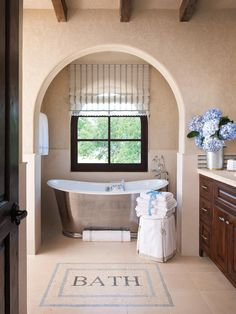 Exposed wood beams and a custom stone mosaic floor bring rustic charm to this bath.  A luxurious, nickel-plated farmhouse style tub framed by an arched entrance becomes the charming focal point of the room.