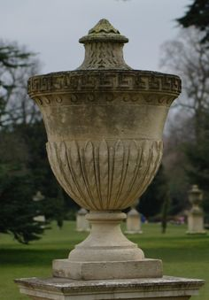 Chiswick House liidded urn in the landscaped grounds by William Kent c1730 the socle with a rising circular foot on a square base, the urn with stiff leaf to the lower body and wave scroll below a greek key frieze above. Portland limestone?