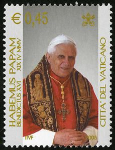 "The 45-cent issue shows the pontiff seated, dressed in red robes with a gold and black stole. The legend on the left is ""Habemus Papam"" or ""We have a Pope."" The 62-cent issue shows Pope Benedict XVI seated, simply dressed is white papal robes."