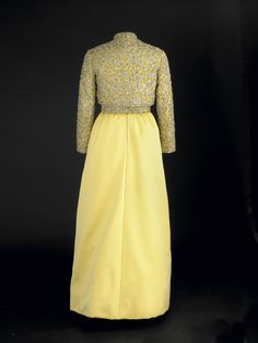 """Pat Nixon wore this mimosa silk satin gown to the 1969 inaugural balls. Designed by Karen Stark for Harvey Berin, it was embroidered in gold and silver and encrusted with Austrian crystals. At the ball held at the Smithsonian Institution, President Nixon announced, """"I like all of Pat's dresses, particularly this one tonight, and, … when she gets finished with it, you'll get it at the Smithsonian."""""""