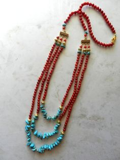 This beautiful, handmade, layered necklace consists of three layers. Each layer consists of red glass beads and real stone turquoise colored