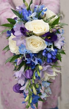 White-with-a-vibrant-twist teardrop bridal bouquet of white avalanche roses, pale purple freesia, dark purple lisianthus, blue gentiana, blue eryngium thistle and blue delphinium. Florissimo - Flowers for weddings, events and businesses in Shropshire and beyond