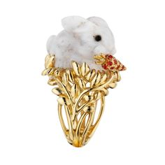Carved white dendritic opal bunny ring in 18k yellow gold, depicting a gray-flecked, white opal bunny munching on a pavé orange sapphire-set carrot, atop an openwork foliate mount.