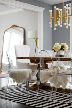 """The dining table is surrounded by fur-covered Lucite chairs. Though they look absolutely chic, the chairs have a functional purpose. (It's easy to clean off little handprints from the clear surface.) Laura unabashedly admits, """"In spite of having a kitchen and dining room I love, we get take-out or eat out almost every day."""""""
