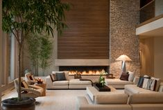 The strong verticality of the great room, accentuated by the towering wood fireplace paneling plays against the low modular sofas. Horizontal wood grain  dry set stone lend contrast and asymmetrical elements.  Photo by George Dzahristos. Schaerer Architextural Interiors Robert Schaerer - Bloomfield Hills, MI