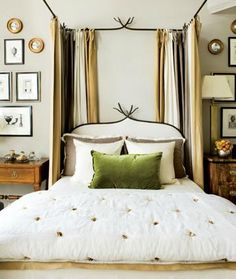 Subtle twig accent in canopied bed with neutral hues in a relaxing and inviting bedroom