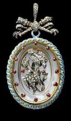 Gold, silver, enamel, rock crystal, diamond, ruby and emerald oval pendant, hanging from rose diamond love trophy of Cupid's wedding torch and quiver of arrows held by a suspension loop. The centre of the rock crystal is encrusted with two rose diamond turtle doves in flight with an emerald and ruby branch of myrtle leaves and berries between them, Paris, c 1860.