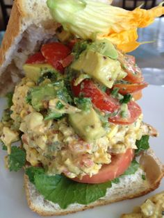 Organic chicken salad with avocado and tomato on baguette