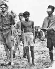 """Aitape, New Guinea. 24 October 1943. A photograph found on the body of a dead Japanese soldier showing, from left to right, NX143314 Sergeant (Sgt) Leonard G. Siffleet of """"M"""" Special Unit with Private (Pte) Pattiwahl and Pte Reharin, Ambonese members of the Netherlands East Indies Forces. The three men are standing blindfolded on open ground and Siffleet has a thin rope tied around his upper body and arms. The three men were executed by order of Vice Admiral Kamada"""