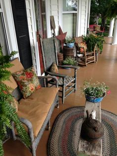 Country farmhouse porch - Unfortunately I can't find the source for this one, but I couldn't resist the gorgeous braided rug and vintage fabric covered pillows.