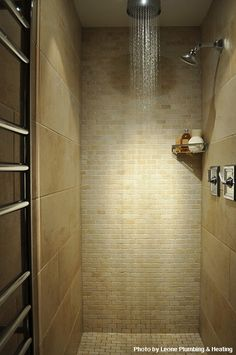 Huge rainfall shower head makes this bathroom remodel a winner in our books. The silver shower door provides a nice contrast to the light brown walls and tile.