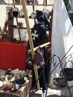 A blacksmiths's booth at the Medieval Festival in Monflaquin displaying replica weapons and armor, as well as hand-crafted leather boots, and fire pit trivets.