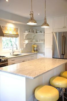 Yellow curtains, mixer, stools, marble counters, white cabinets