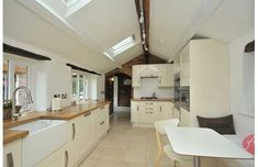 A traditional Shaker kitchen in Farrow and Ball Pale Hound. The roof lanterns flood light into the room.